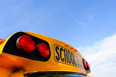 Upper front of yellow school bus lights and sign against empty sky.