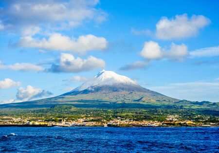 Mount Pico volcano western slope and town of Madalena viewed from ocean under blue sky and clouds, in Azores, Portugal. Фото со стока