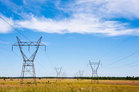Na polach wiejskich pod częściowo zachmurzonym niebem duże wieże przesyłu energii elektrycznej i linie energetyczne cofają się w oddali.