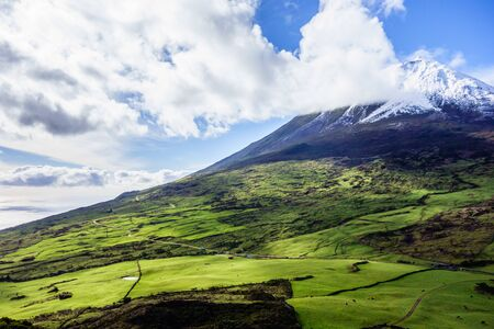 Mount Pico volcano summit and southern slope under blue sky and clouds, in Azores, Portugal.