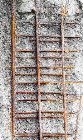Rusted girders exposed in weathered concrete.