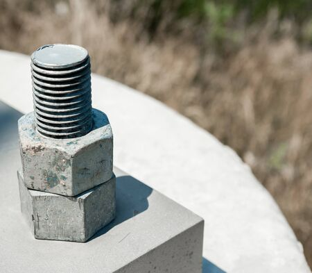 Two hexagonal steel nuts threaded on bolt attached to concrete block.