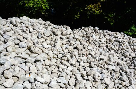 Pile of gray rocks and gravel illuminated near trees in shadow.