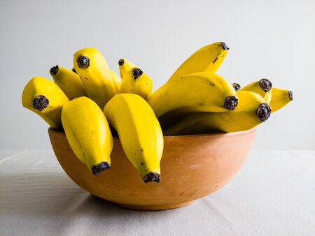 Many yellow bananas in brown ceramic bowl on table, viewed from side.