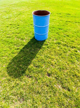 Single blue metal bin casting shadow on green grass field.