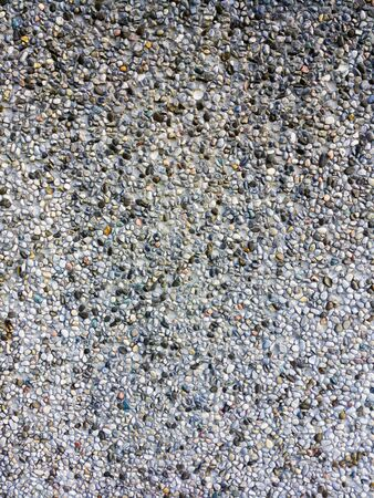Abstract background pattern of colored pebbles in cement wall.
