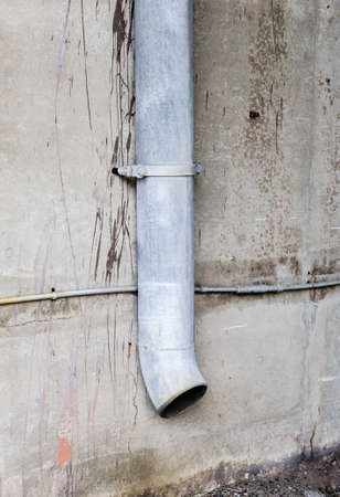 Vertical drain pipe mounted on dirty cement wall.