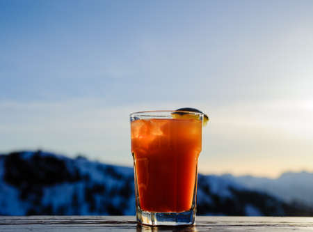 Illuminated glass containing orange cocktail drink with lime wedge against blurry mountains. Фото со стока