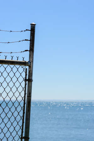 Edge of chain link fence and barbed wires against water and clear blue sky.