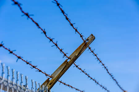 Focus on part of rusted metal barb wire fence against blue sky.