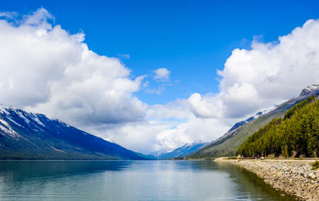 Lake in valley between mountains under clouds and sky, at Moose Lake, British Columbia, Canada.