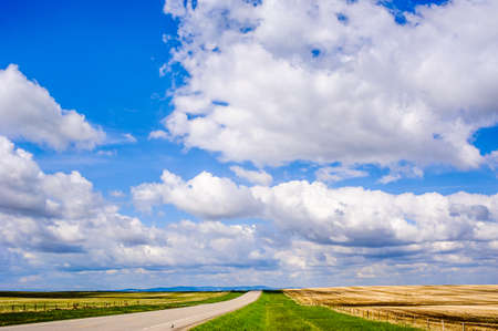 Straight empty road on prairie under blue sky and low clouds, in Alberta, Canada. Фото со стока