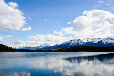 Small lake before mountains under clouds and sky, in Jasper, Alberta, Canada. Фото со стока
