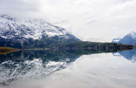 Mountain reflected in still lake under cloudy sky, at Waterton Lakes, Alberta, Canada.