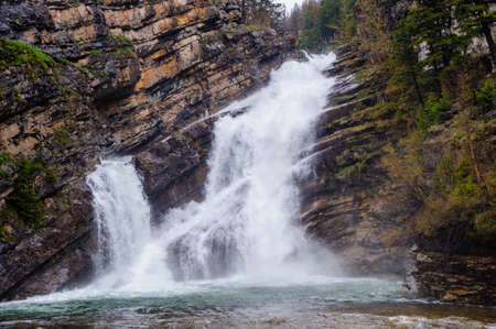 Waterfall cascading over diagonal rock layers.