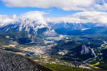 Town and surrounding mountains under low clouds, in Banff, Alberta, Canada.