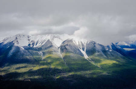 Forested mountains and valley under low clouds, near Banff, Alberta, Canada.
