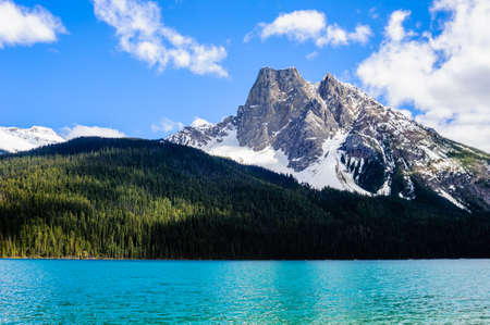Mountain rising out of dark forest near blue lake under  sky and clouds, at Emerald Lake, British Columbia, Canada. Фото со стока