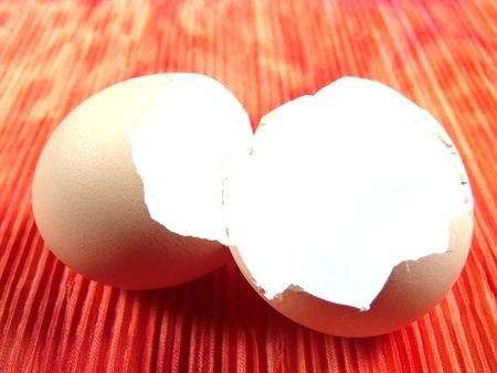 Empty Egg shell on top of a piece of tie dye cloth (vibrant color background) photo