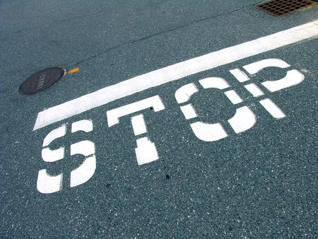 road surface: A big traffic stop sign painted on the road surface