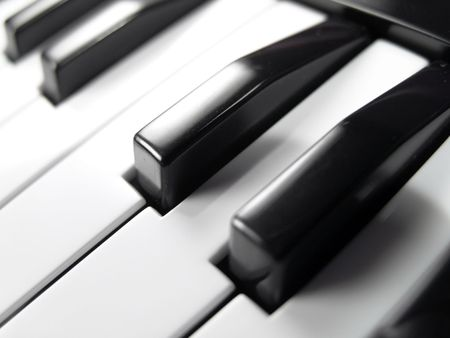 Close-up of black and white keys on a piano keyboard (focus on one key in the middle)