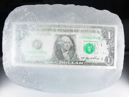 downsizing: US paper currency (one dollar) frozen in ice representing a downsizing economy, financial crisis, unemployment and investment lose