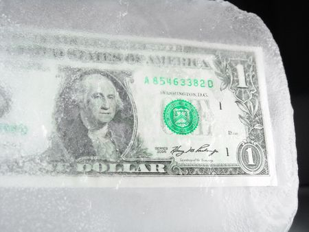 US paper currency (one dollar) frozen in ice representing a downsizing economy, financial crisis, unemployment and investment lose