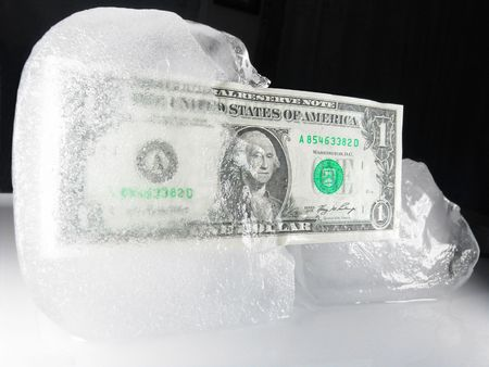 US paper currency (one dollar) in half frozen ice representing a current downsized economy, financial crisis, unemployment and investment lose.  Ice melting could also mean the economy is getting better, coming out from a prior frozen state.               Standard-Bild