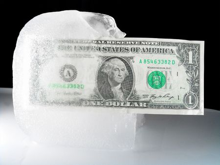 getting better: US paper currency (one dollar) in half frozen ice representing a current downsized economy, financial crisis, unemployment and investment lose.  Ice melting could also mean the economy is getting better, coming out from a prior frozen state.               Stock Photo
