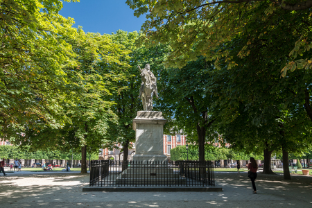 citytrip: Paris, France - August 13, 2016: Statue of Louis XIII on the Place des Vosges in Paris. This place is the oldest planned square in Paris and one of the finest in the city.