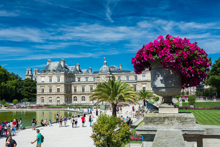 citytrip: Paris, France - August 14, 2016: The Luxembourg garden covers 23 hectares and is known for the Luxembourg palace, its lawns, tree-lined promenades, flowerbeds, the model sailboats on its circular basin, and for the picturesque Medici Fountain