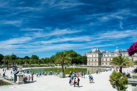 Paris, France - August 14, 2016: The Luxembourg garden covers 23 hectares and is known for the Luxembourg palace, its lawns, tree-lined promenades, flowerbeds, the model sailboats on its circular basin, and for the picturesque Medici Fountain