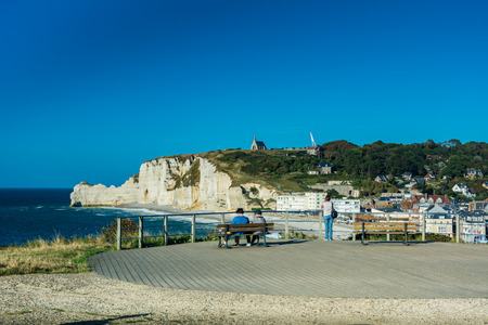 normandy: Etretat, France - September 8, 2016: Etretat is best known for its chalk cliffs, including three natural arches and a pointed formation called LAiguille or the Needle, which rises 70 metres above the sea.
