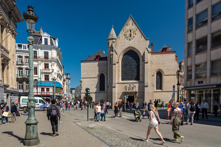 Brussels, Belgium - May 5, 2018 : People walking near St. Nicholas Church. It is a delightful little church behind the Bourse in Brussels. It is surrounded by fine old houses that seem to huddle under it.