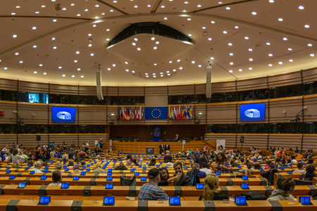 Brussels, Belgium - May 5, 2018 : People visiting the interior of the European Parliament hemicycle (debating chamber) in Brussels. The European Parliament is the directly elected parliamentary institution of the European Union.