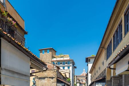 Florence, Italy - June 5, 2019 : The Ponte Vecchio (Old Bridge) is a medieval stone closed-spandrel segmental arch bridge over the Arno River, noted for having shops built along it. The present tenants are jewelers, art dealers and souvenir sellers. Archivio Fotografico