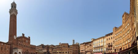 Siena, Italy - June 7, 2019 : The Torre del Mangia is a tower located in the Piazza del Campo, adjacent to the Palazzo Pubblico (Town Hall). When built it was one of the tallest secular towers in medieval Italy.