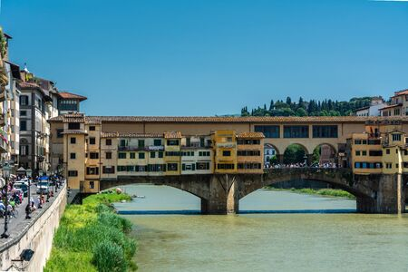 Florence, Italy - June 5, 2019 : The Ponte Vecchio (Old Bridge) is a medieval stone closed-spandrel segmental arch bridge over the Arno River, noted for having shops built along it. The present tenants are jewelers, art dealers and souvenir sellers. Editoriali