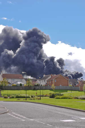 Dark smoke cloud rising over residential area