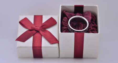Gift box with red ribbon an silver ring Stock Photo
