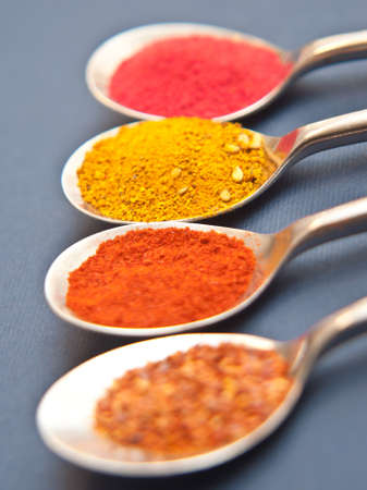 Fours spices presented in teaspoons over dar blue background Stock Photo