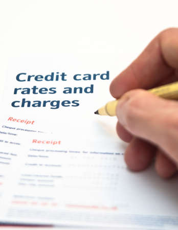 Hand holding pen over credit card charges Stock Photo