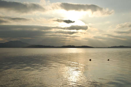 Sun shining through clouds on Loch Lomond Stock Photo