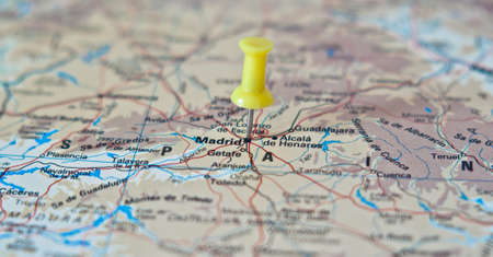 Push pin pointing at Madrid, Spain on a map