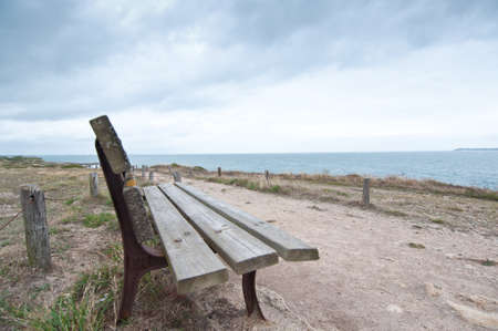 Wooden bench facing the sea on a cloudy day Stock Photo