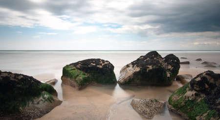 Beach rocks long exposure with cloudy sky Stock Photo