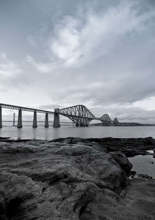 Black and White Forth Rail Bridge with foreground rocks in Scotland photo