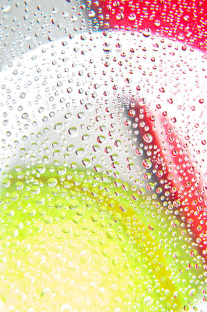 Water droplets on glass with background yellow and red colors