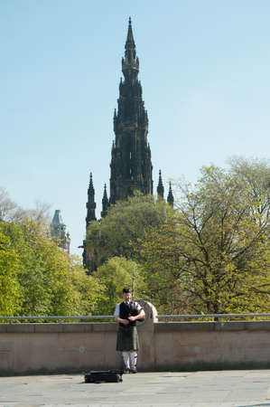 Edinburgh May 2012: Scottish Piper playing with Edinburgh Scott Monument in the background Stock Photo - 14138303