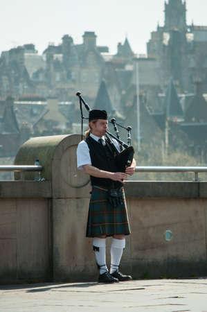 Edinburgh May 2012: Scottish Piper playing with Edinburgh city background